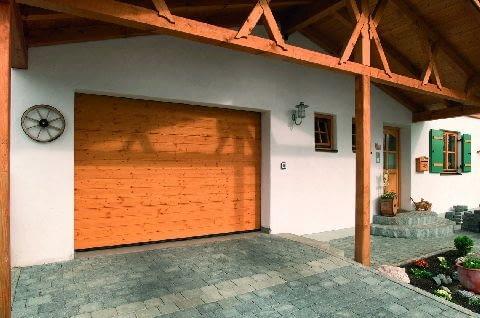 Tradycyjna, szara, betonowa kostka dobrze komponuje się z drewnianymi elementami wykończenia domu
