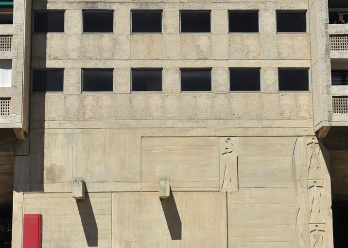 """Jednostka Marsylska, proj. le Corbusier - detale na dziedzińcu wschodnim. Od lewej - """"stela miar"""" odzwierciedlająca dwie serie Modulora, ławka, kamień węgielny. Na fasadzie budynku widoczne okno z foyer, oraz sylwetki nazwane przez Le Corbusiera """"Widmami Modulora"""""""