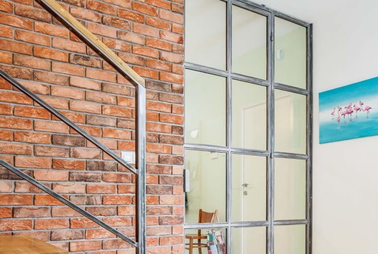 Do podzielenia tej przestrzeni wykorzystano szkło zamknięte w metalowe ramy. Taki zabieg o nieco industrialnym charakterze świetnie sprawdza się w nowoczesnej przestrzeni i zapewnia dopływ naturalnego światła