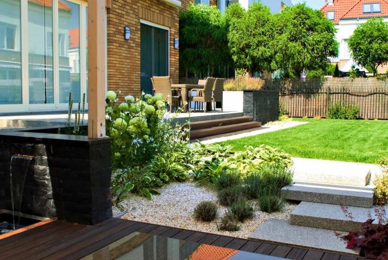KAMIENNE SCHODY łączą zaciszną altanę z prostokątnym trawnikiem pod tarasem.