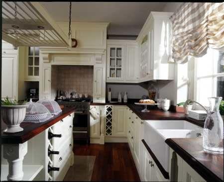Jak w kuchni prababci. Kuchenka obudowana trawertynem i bukowymi szafkami wygląda jak wiejski piec. Motyw przewodni wnętrza to fantazyjnie rzeźbione kolumny.