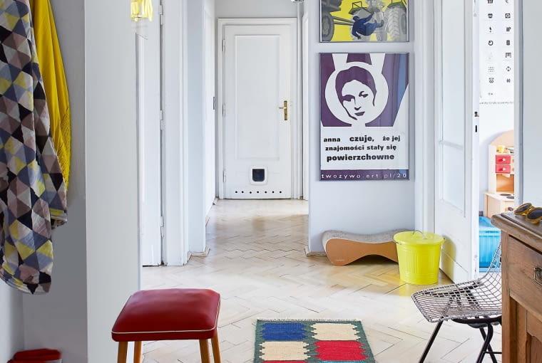 Galeria w przedpokoju, a w niej plakaty BHP z lat pięćdziesiątych i sitodrukowa praca grupy Twożywo, legendy polskiego street artu, pamiątka po artystycznej akcji, w której brała udział Ania. Lampa sufitowa z metalowych prętów, odziedziczona po dawnych lokatorach, pochodzi z czasów PRL-u, minineon na ścianie to współczesny wyrób. Czerwony stołek pochodzi z nieistniejącego już sklepu z meblami retro.