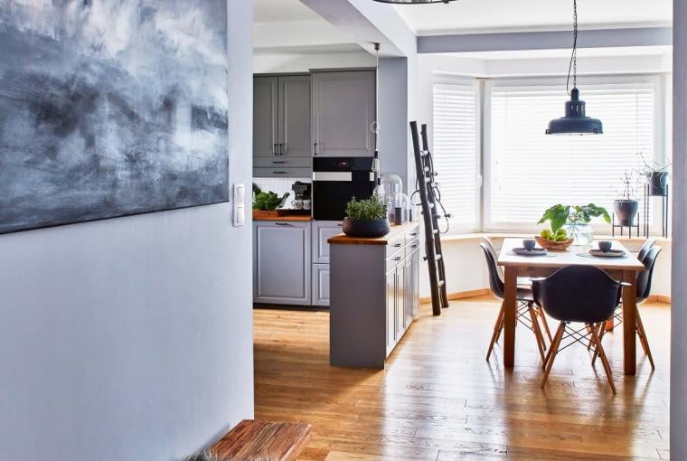 Płytkie szafki kuchenne pełniące funkcję barku symbolicznie odgradzają kuchnię od salonu. Na podłodze położono bielone dębowe deski. Na pierwszym planie wisi lampa z tej samej serii co ta nad stołem. Autorką obrazu jest Margo Hupert.