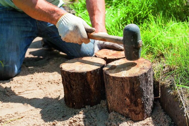 Na dno sypiemy piasek warstwą o grubości ok. 5 cm, wyrównujemy i wbijamy gumowym młotkiem pniaki o wysokości ok. 30 cm.