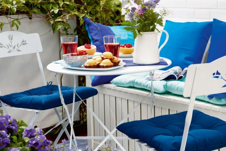 bA table laid on a sunny balcony with lightweight, space-saving folding furniture and a bench chest
