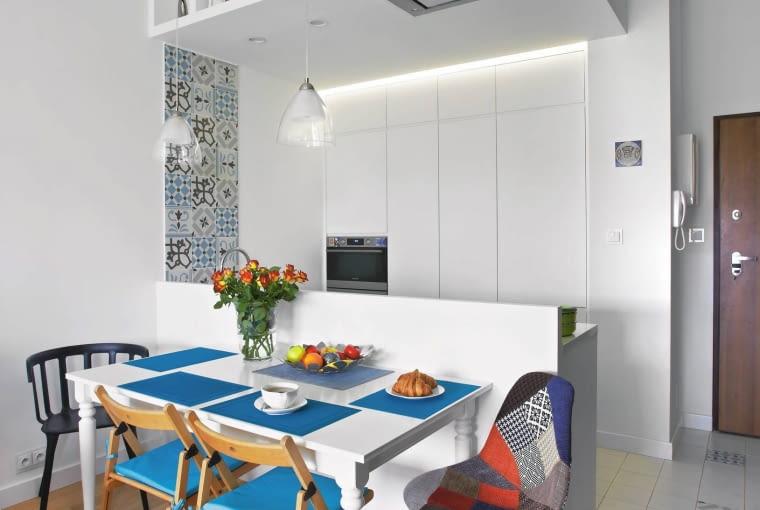 Spory stół postawiono przy ściance wydzielającej aneks kuchenny