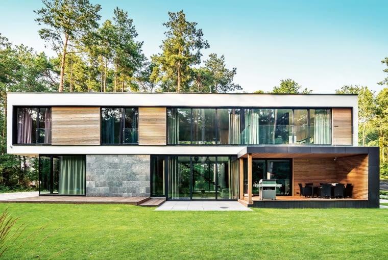 Zieleń, zarówno ta ogrodowa, jak i naturalna leśna, świetnie koresponduje z ascetycznym charakterem budynku