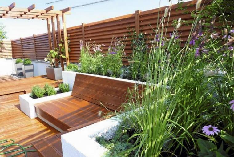 Rośliny balkonowe. Użycie drewna w ciepłym kolorze sprawia, że taras sprawia przytulne wrażenie. Będzie tu jeszcze ładniej, gdy pergolę oplecie winorośl