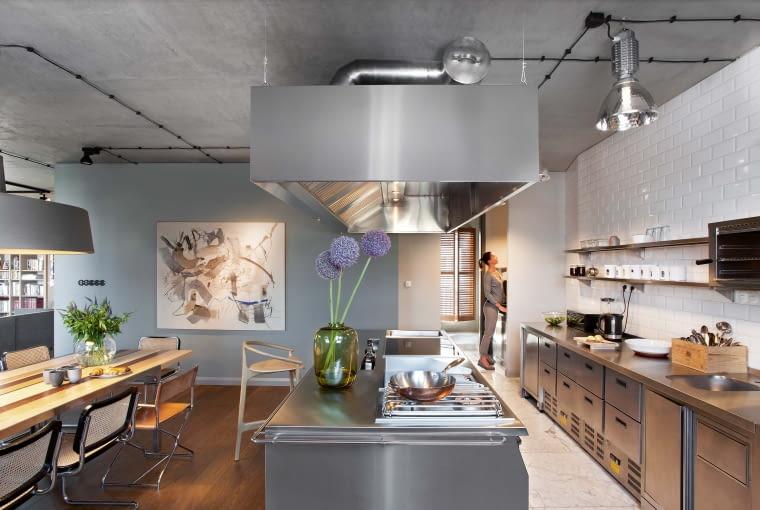 Technologiczna kuchnia z długim ciągiem roboczym i wielofunkcyjną wyspą projektu Katarzyny Kuchejdy. Ściana w głębi oddziela strefę kuchenno--jadalnianą od salonu.