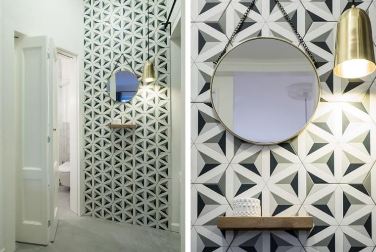 W przedsionku zawisło okrągłe lustro w pozłacanej ramie. Na ścianie wykorzystano tapetę z geometrycznym wzorem.