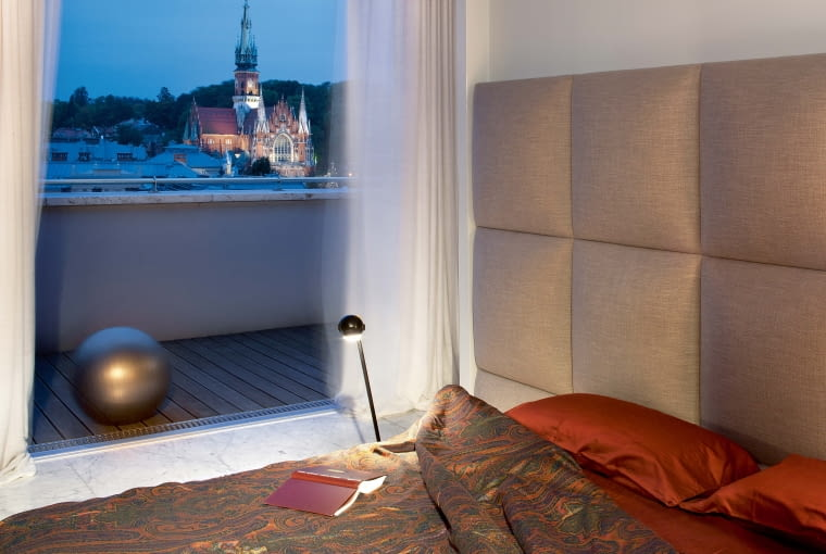 Miejski pejzaż na dobranoc: wieża kościoła św. Józefa wznosząca się nad dachami Podgórza. Łóżko James (Comforty), lampka nocna (Reflex-Studio).