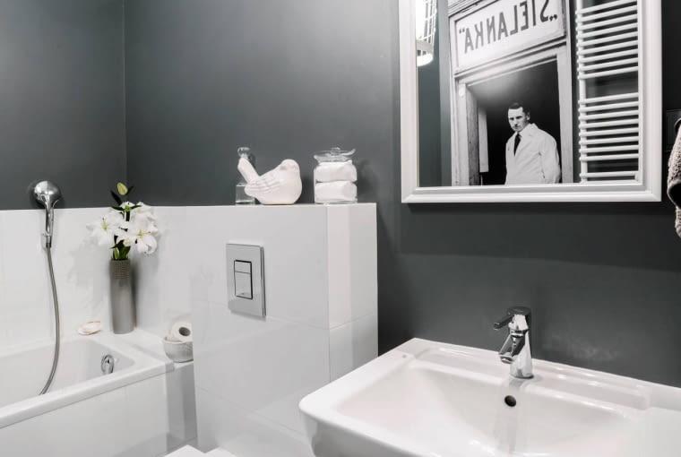 ŁAZIENKA. Szare ściany ożywia biel sufitu, mebli i urządzeń. Łazienka została zaaranżowana prosto i minimalistycznie, bez zbędnych sprzętów i dodatków.