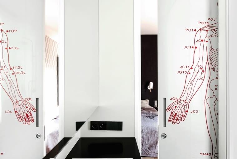 W łazience rządzi kontrast czerni i bieli. Na chowanych w ścianie przesuwanych drzwiach mapa energetyczna ludzkiego ciała - grafika według projektu Marii Widelak. Nad umywalką (Alape) bateria Pan (Zucchetti).