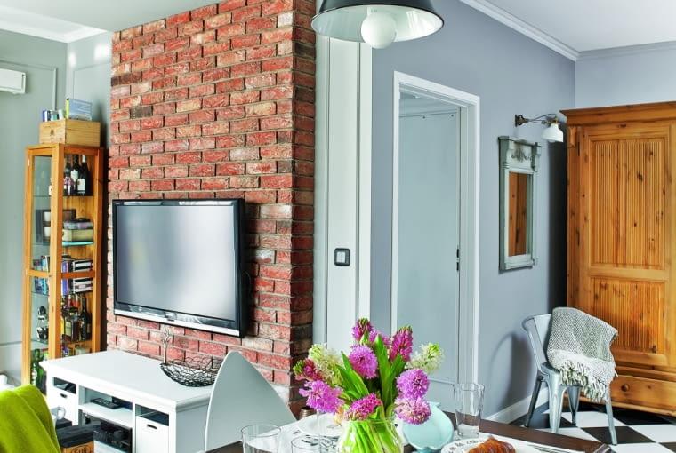 Mocne wzory: spokojne szarości ożywia intensywna barwa cegły orazczarno-białe romby na podłodze. Wiekowa szafa ilustro wdrewnianej ramie pochodzą ztargu staroci wmiasteczku Czacz. Żyrandol jest zIKEA. Metalowe loftowe krzesło projektantka wypatrzyła wsklepie design24.com.pl.