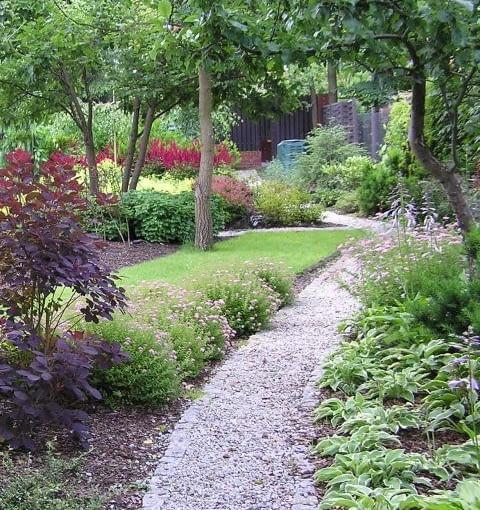 Przykładem nawierzchni ogrodowej może być także ścieżka żwirowa w obrzeżu z kostki granitowej. Projektowanie ogrodu