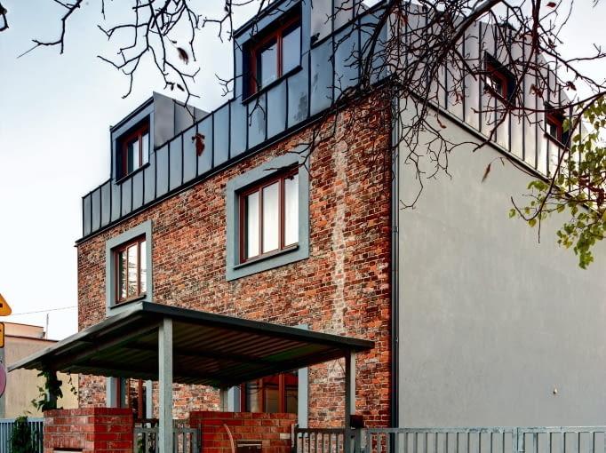 Dom po przebudowie. Budynek od strony ulicy. Surowość formy ceglanego muru podkreśla dodatkowo blacha na elewacjach oraz stalowe ogrodzenie