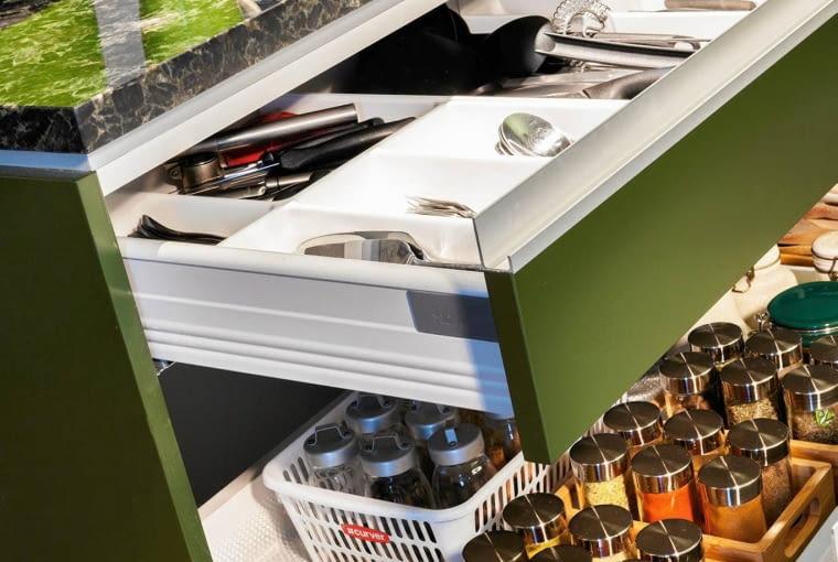 PRZECHOWYWANIE W KUCHNI. W szufladzie tuż pod blatem roboczym umieszczono wkłady na sztućce i inne drobne akcesoria. Szuflada niżej jest przeznaczona na liczne pojemniczki z przyprawami - od razu widać, że w tym domu dużo się gotuje!