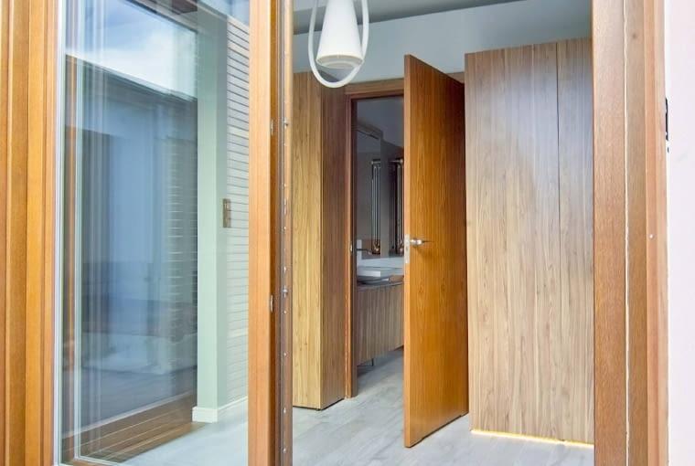 Posadzka z gresu imitującego betonowy szalunek 'przepływa' między łazienką, holem i tarasem, wydłużając optycznie wnętrze. Projekt i realizacja: Lorens, www.lorenslorens.pl