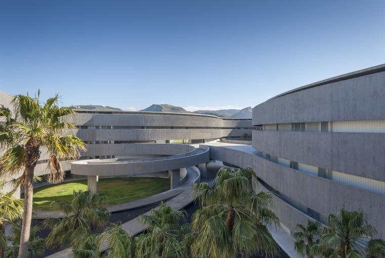 Wydział Sztuk Pięknych, Uniwestytet w La Laguna, Teneryfa, Hiszpania, proj. gpy arquitectos, nominacja w kategorii budynńki zrealizowane, szkolnictwo wyższe i nauka. Niezwykły budynek jest rozbudową istniejącego kampusu. Rozszerzenie pozwoliło wykreować wewnętrzną, zamkniętą przestrzeń stanowiącą rodzaj dziedzińca na potrzeby Uniwersytetu. Ta zielona przestrzeń została otoczona półotwartymi spiralami korytarzy, które pozwalają na swobodne obchodzenie dziedzińca i oglądanie go z różnych perspektyw, a cała podróż dzięki kolistym kształtom zdaje się nie mieć końca i pozbawiona jest jakichkolwiek przerw i granic.