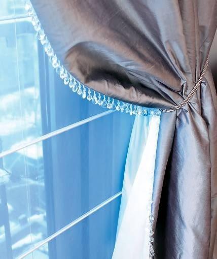 DEKORACJE OKIEN - STYLOWE FAŁDY. Sznur pełni też funkcję praktyczną - podtrzymuje zasłony z boku drzwi balkonowych. Brzegi zasłon wykończono taśmą z przezroczystymi wisiorkami.