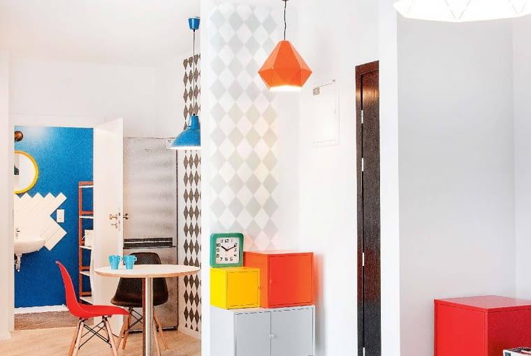 Wybór lamp nie jest przypadkowy. Pomarańczowa pasuje do szafki w przedpokoju, niebieska do ściany w łazience, a czarna -do drzwi. Wszystkie kupiono w sklepie jasnociemno.pl. Ściana wkąciku jadalnym również została pokryta tapetą wromby - taką samą jak ta nad szafkami kuchennymi, co optycznie scala tę część mieszkania. Ciemne drzwi to przemyślany wybór Gaby - inaczej strefa wejściowa byłaby jedną białą plamą.