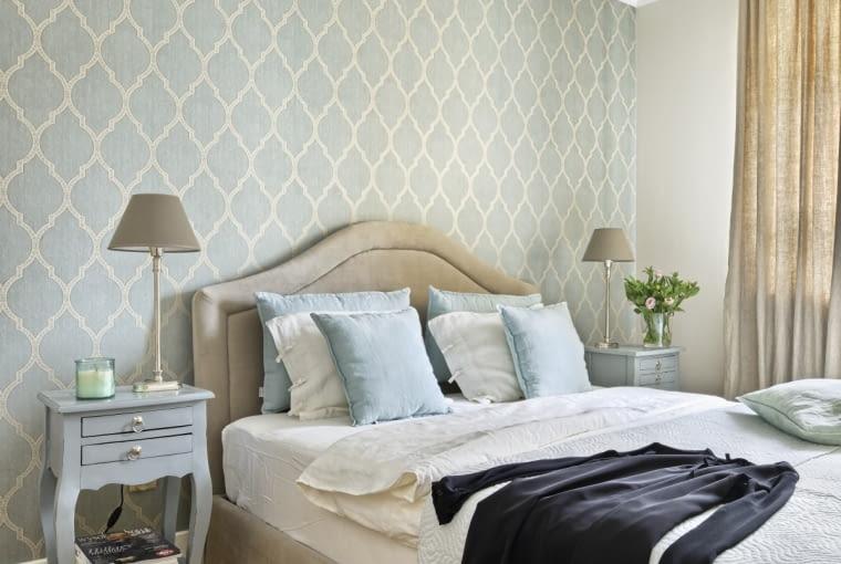 W sypialni króluje bladoniebieski odcień. Widać go na tapecie zwzorem marokańskiej koniczynki, poduszkach (twojerolety.pl) i szafkach nocnych (House & More). Drewniana podłoga jest staranie odnowiona - wycyklinowana i pokryta najpierw olejem, a potem specjalnym lakierem nadającym jej odporność na zarysowania.