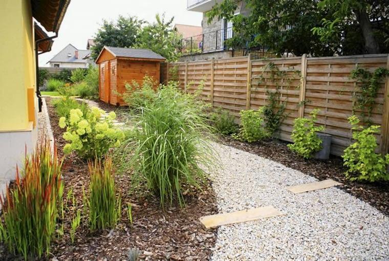Projekt ogrodu w nowym stylu. Przy ogrodzeniu stoi domek na narzędzia ogrodnicze