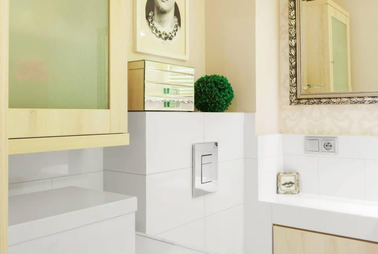 TUŻ PRZY SEDESIE zamontowano pod blatem jedynie szufladę - szafki nie dałoby się otworzyć. Obudowana ścianka instalacyjna służy jako półka na dekoracyjne dodatki.