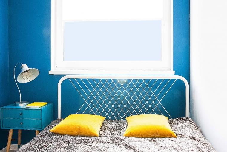 Szafka nocna powstała zmałego biurowego sejfu. Projektantka pomalowała go na niebiesko (na inny odcień niż ściana, żeby mebelek nie zlewał się ztłem) idorobiła drewniane nogi. Ażurowy zagłówek łóżka (IKEA) pasuje do tapet w romby. Jak widać, również charakter sypialni jest spójny z wystrojem całego mieszkania.