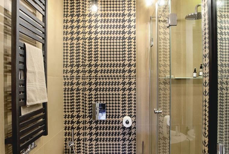 Pepitka dobrze się prezentuje nie tylko na płaszczu - drugą, mniejszą łazienkę (z kabiną prysznicową) również zdobią płytki z Art Design. Prosty grzejnik kupiono w superidea.com.pl, lampę-pająka w westwing.pl.