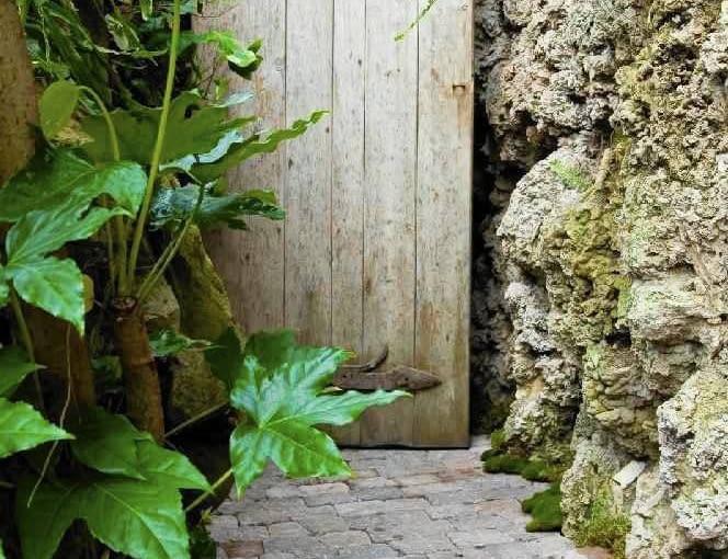 DO TEGO POZORNIE ZAPOMNIANEGO ZAKĄTKA pasuje ścieżka ułożona z postarzanej kostki betonowej oraz wiekowe drzwi, znalezione na... śmietniku.