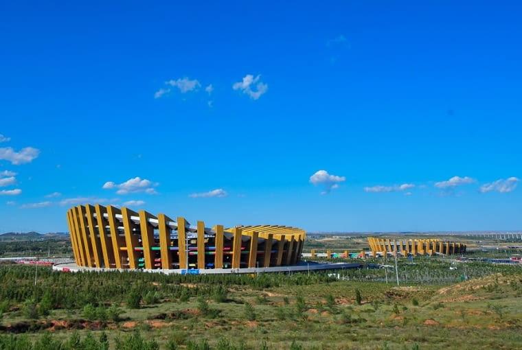 Ordos Sports Center Stadium, Ordos - Chiny (VII nagroda w głosowaniu jury) - Pomiędzy kolumnami przebijają się intensywne barwy czerwieni i zieleni podtrybunia, które odnoszą się do witalności lokalnej ludności oraz energii płynącej ze sportu.