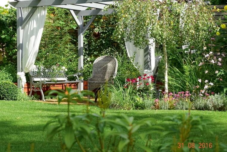 Na placyku wypoczynkowym wznosi się pergola otoczona podwyższoną rabatą z różami, lawendą i ziołami.