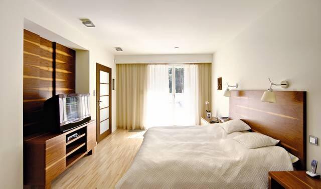 Sypialnia gospodarzy. O jej charakterze zadecydowały eleganckie drewniane panele z drewna orzecha amerykańskiego, oraz stonowana kolorystyka, w jakiej utrzymano wszystkie elementy wystroju wnętrza