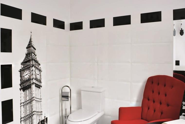 DOM. W czarno-białej toalecie na parterze dla żartu stanął czerwony fotel i stolik, w sam raz, żeby chwilę odpocząć, podziwiając Big Bena (kolekcja płytek Londyn Macieja Zienia zaprojektowana dla Tubądzina).