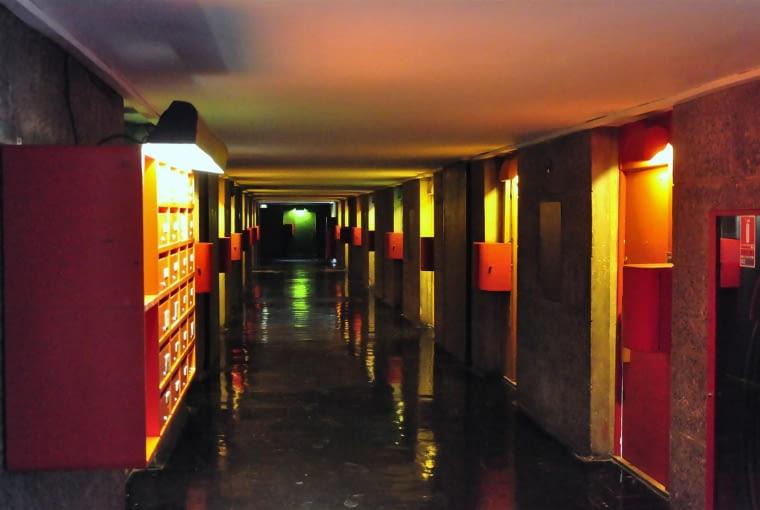 """Jednostka Marsylska, proj. Le Corbusier - """"wewnętrzna ulica"""" czyli korytarz i wejścia do lokali. Widoczne są skrzynki, umożliwiające dostarczanie lokatorom produktów takich jak gazety czy mleko oraz skrzynki pocztowe. """"Wewnętrzne ulice"""" są oświetlone sztucznie, atmosfera na nich jest dość ponura i ze względu na niski strop - klaustrofobiczna. Wrażenia te potęguje czarna, błyszczącą podłoga"""