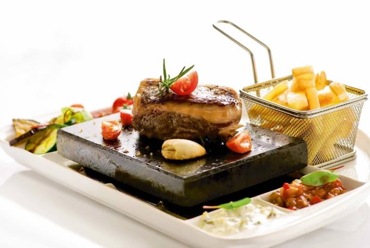 Polędwica wołowa na gorącym kamieniu z frytkami, grillowanymi warzywami, domowymi sosami i majonezem truflowym