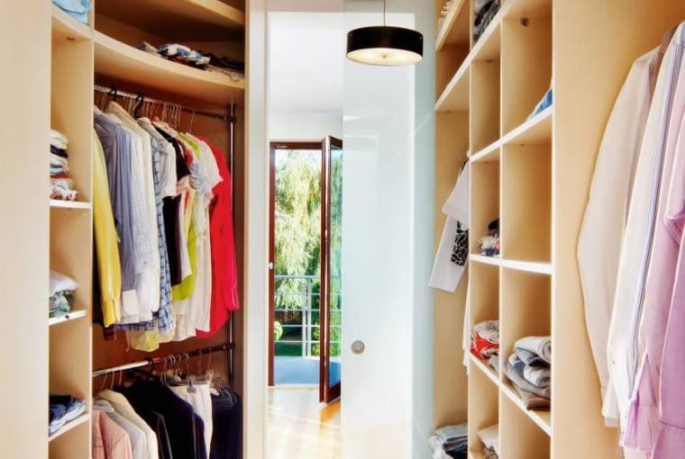 Zabudowa garderoby powstała na wymiar z laminowanej płyty imitującej drewno bukowe. Wnętrze oświetlają dwie lampy sufitowe o takiej samej formie jak te w sypialni, tyle że mniejsze.