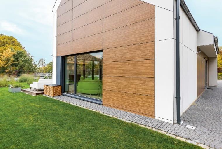 Otwarty na otoczenie dom stoi w starannie zagospodarowanym, choć młodym ogrodzie. Za kilka lat zieleń będzie z pewnością znacznie bardziej bujna