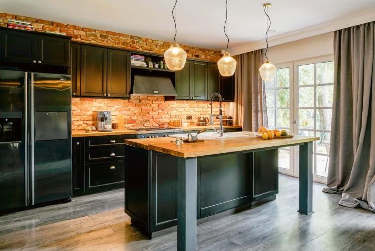 Metal i drewno kuchennych mebli skontrastowane zostały z surową cegłą, a całość dopełniają trzy lampy 'nadlatujące' z sufitu
