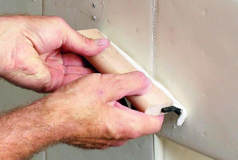 Płytkę przyklejamy do ściany, dokładnie dociskając krawędzie. Po kilkunastu minutach szczeliny wokół kafelka wypełniamy dopasowaną kolorystycznie zaprawą do spoinowania.