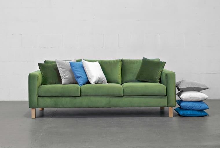 Sofa Kera to połączenie prostej formy i wygody. Występuje w różnych rozmiarach i obiciach, m.in. w aksamitnej tkaninie o głębokim odcieniu zieleni.