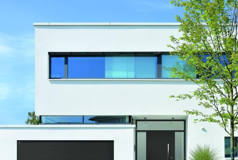 Dobry przykład architektury nowoczesnej: stolarka o spójnej, zdecydowanej kolorystyce mocno kontrastuje z białą, surową elewacją