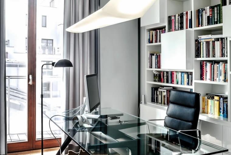 """Okno gabinetu wychodzi na północ. Rozjaśniają go lekkie formy, dużo bieli i przejrzystych """"niewidzialnych"""" materiałów. Przy szklanym biurku T-NO.1 (Fritz Hansen) krzesło Aluminium Group Executive duetu projektowego Eamesów. Lampa nad blatem Mouette (Artemide)."""