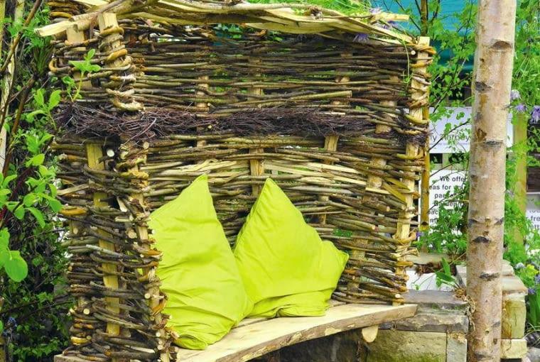 Drewno w ogrodzie. Oryginalna altanka dla dwojga - upleciona z gałęzi, wparta na 'kurzej nóżce' z wykopanej karpy