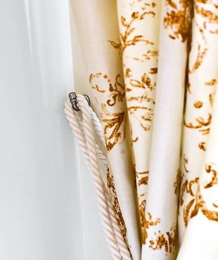 DEKORACJE OKIEN - ROMANTYCZNA SYPIALNIA. Zasłonę uszyto z białej lnianej tkaniny z nadrukowanym deseniem o barwie starego złota.