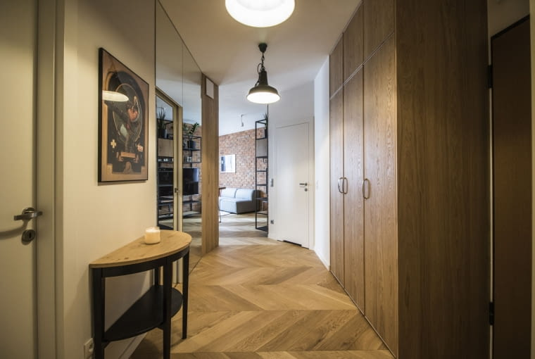 Łamany kształt ma nie tylko salon, ale również korytarz. Duża tafla lustra odbija światło, rozjaśniając wnętrze.