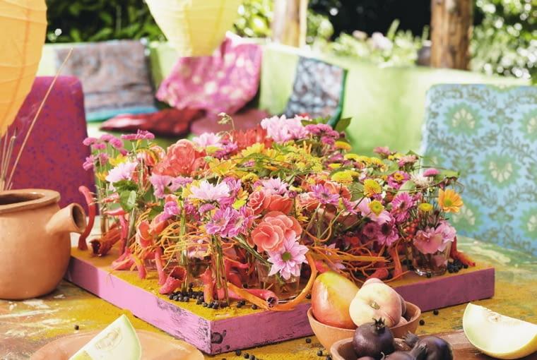 Orientalne kompozycje kwiatowe. Płaska kompozycja z begonii, alstremerii i chryzantem udekorowana barwionyni kawałkami drewna