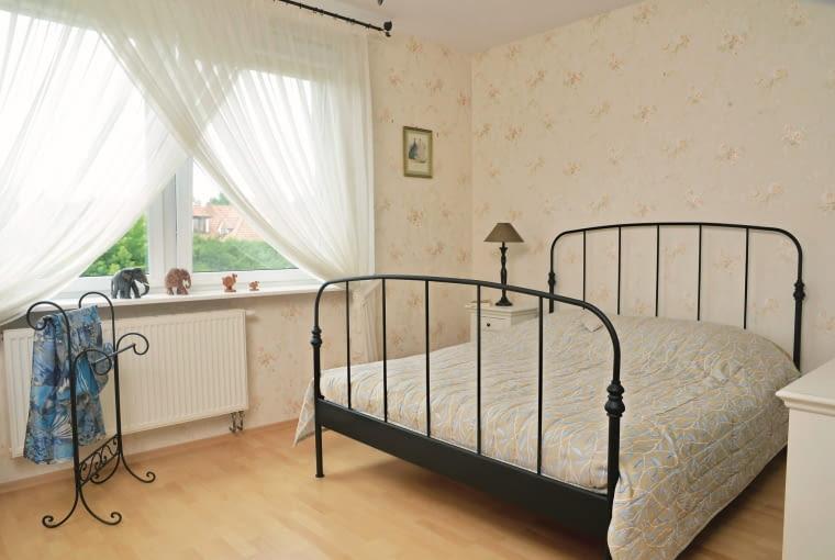 DOM. W sypialni, jak mówi gospodyni, mogłaby zamieszkać Ania z Zielonego Wzgórza. Pewnie spodobałaby się jej kremowa tapeta w kwiaty, kuta rama łóżka, karnisz i stojący wieszak.