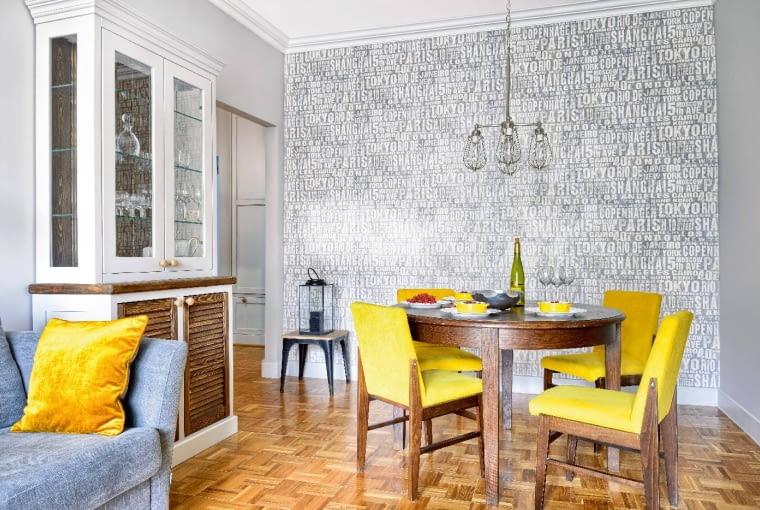 MEBLE ZRECYKLINGU: krzesła (prezent od rodziców Anety) irozkładany stół (pierwszy zakup do nowego mieszkania) pochodzą zlat sześćdziesiątych. Pasują do nich współczesne sprzęty - kanapa (zFurninova) oraz kredens zgałkami zplecionego sznurka i regał zaprojektowane przez Macieja Kocója. Lampa nad stołem została kupiona wHouse & More.